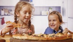 Gulliga flickabästa vän för litet barn som skrattar och äter pizza Lyckligt barndom- och matbegrepp royaltyfria bilder