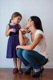 Gulliga flickablickar på hennes mamma med att älska synar Royaltyfri Bild