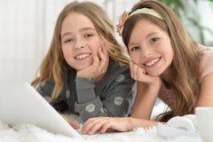 Gulliga flickor in med bärbara datorn Royaltyfria Foton