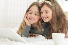Gulliga flickor in med bärbara datorn Fotografering för Bildbyråer