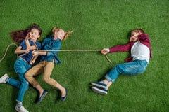 Gulliga flickor och pojke som ligger på gräs och spelar dragkampen Arkivfoto