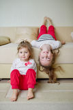 Gulliga flickor på den uppochnervända soffan Arkivbilder