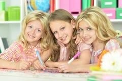 Gulliga flickor som drar med blyertspennor Fotografering för Bildbyråer