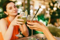 Gulliga flickor som firar natt ut med coctaildrinkar royaltyfri fotografi