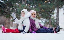 Gulliga flickor som har gyckel bland vinter, parkerar Arkivbilder