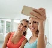 Gulliga flickor som hemma tar selfies arkivfoto