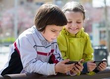 Gulliga flickor som poserar med mobiler Arkivbild