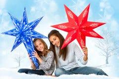 Gulliga flickor som rymmer pappers- stjärnor Arkivbilder