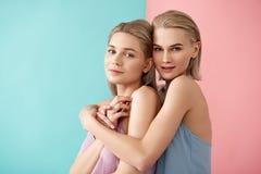 Gulliga flickor som står i en kram Arkivbild