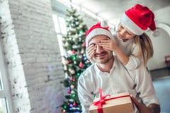 Gulliga glade stängande faders för dotter ögon med handen som ger gåvaasken royaltyfri foto