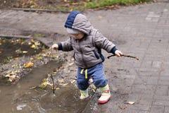 Gulliga iklädda kängor för ett årslitet barn och gummiflåsanden som hoppar i en pöl Rolig unge med lycka för barn` s Royaltyfri Bild