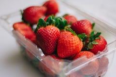 Gulliga jordgubbar i en plast- korg på en vit bakgrund Royaltyfri Bild