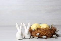 Gulliga keramiska kaniner nära dekorativt rede med påskägg på tabellen royaltyfria bilder