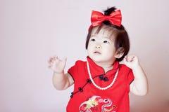 Gulliga kinesiska små behandla som ett barn i röd cheongsam Arkivbilder