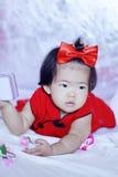 Gulliga kinesiska små behandla som ett barn i röd cheongsam har gyckel Arkivbild