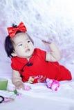 Gulliga kinesiska små behandla som ett barn i röd cheongsam har gyckel Arkivfoto