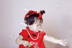 Gulliga kinesiska små behandla som ett barn i röda cheongsamleksåpbubblor Arkivfoton