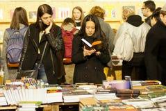 Gulliga kvinnor som läser nya böcker i folkmassa av avläsare Arkivfoton