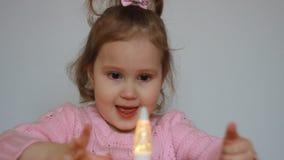 Gulliga lekar för ett barn med en ficklampa och blickar på det mångfärgade skenet och ljuset från det Härlig flicka som rymmer a stock video