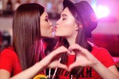 gulliga lesbiska flickvänner som kysser på stångbakgrund på ett parti royaltyfri foto
