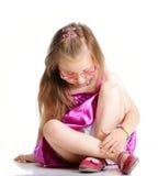Gulliga liten flickaexponeringsglas som sitter på det isolerade golvet Royaltyfri Bild