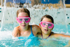 Gulliga lyckliga flickor i rosa skyddsglasögonmaskering i simbassängen Arkivfoton