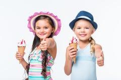 gulliga lyckliga små flickor i swimwear som äter glass royaltyfria foton