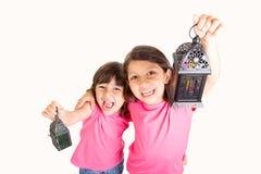 2 gulliga lyckliga unga flickor som firar Ramadan med deras lyktor Fotografering för Bildbyråer