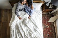 Gulliga mellan skilda raser par på kyssa för säng Royaltyfria Bilder