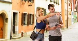 Gulliga millennial par som finner deras väg runt om en ny stad arkivfoton