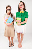 Gulliga nerdy flickor som rymmer böcker Royaltyfri Fotografi