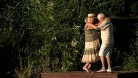 Gulliga par av pensionärer som utomhus dansar stock video