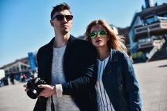 Gulliga par i sunglass som går på gatan med kameran Royaltyfri Bild