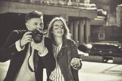 Gulliga par i sunglass som går på gatan med kameran BW Royaltyfri Foto