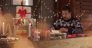 Gulliga par i vintertröjor som slår in julklappar arkivfilmer