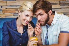Gulliga par på ett datum som delar ett exponeringsglas av orange fruktsaft Arkivbilder