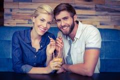Gulliga par på ett datum som delar ett exponeringsglas av orange fruktsaft Royaltyfria Foton