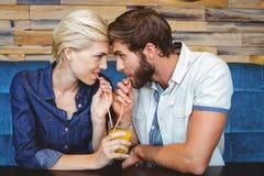 Gulliga par på ett datum som delar ett exponeringsglas av orange fruktsaft Royaltyfri Foto