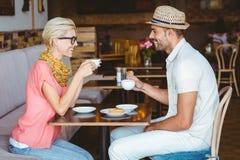Gulliga par på ett datum som talar över en kopp kaffe Arkivfoto
