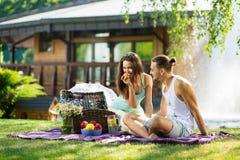 Gulliga par som äter äpplet på picknicken som ler på de Arkivfoto