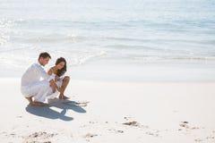 Gulliga par som drar en hjärta i sanden Arkivfoto