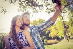 Gulliga par som gör selfie med den retro kameran i parkera Royaltyfria Foton