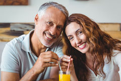 gulliga par som har exponeringsglas av orange fruktsaft Royaltyfria Bilder