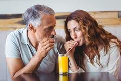 gulliga par som har exponeringsglas av orange fruktsaft Arkivbilder