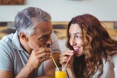 gulliga par som har exponeringsglas av orange fruktsaft Arkivbild