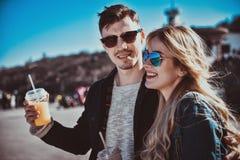Gulliga par som har gyckel och att gå på gatan och, dricker coctailar royaltyfria foton