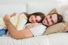 Gulliga par som kopplar av på soffan Fotografering för Bildbyråer