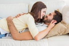 Gulliga par som kopplar av på soffan Arkivbilder