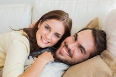 Gulliga par som kopplar av på soffan Royaltyfria Bilder