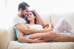Gulliga par som kopplar av på soffan Arkivfoto